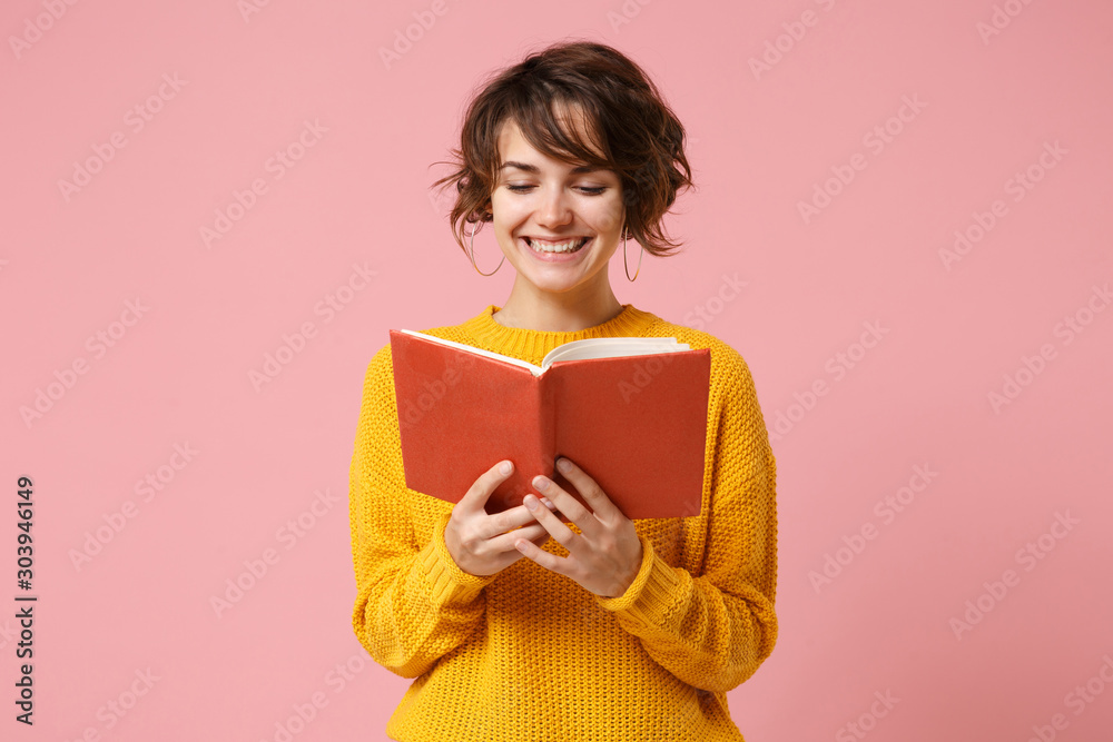 Fototapeta Smiling young brunette woman girl in yellow sweater posing isolated on pink wall background, studio portrait. People sincere emotions lifestyle concept. Mock up copy space. Holding and reading book.