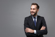 Smiling young business man in classic black suit shirt tie posing isolated on grey background. Achievement career wealth business concept. Mock up copy space. Holding hands crossed, looking aside.