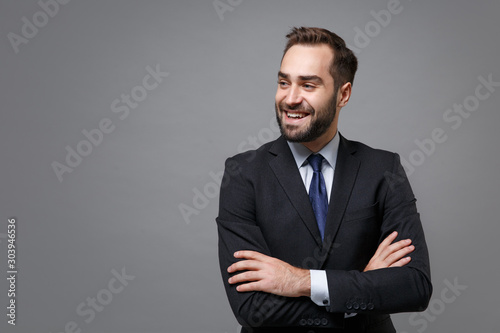 Fototapeta Smiling young business man in classic black suit shirt tie posing isolated on grey background. Achievement career wealth business concept. Mock up copy space. Holding hands crossed, looking aside. obraz na płótnie