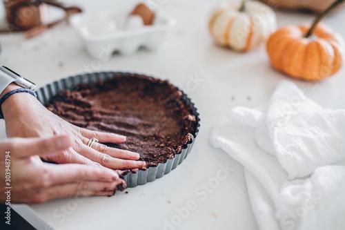 Woman using hands to fill pie crust tin Wallpaper Mural