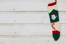Hand Knitted Christmas Stocking Hanging On A Weathered Wood Plank Wall With Copy Space