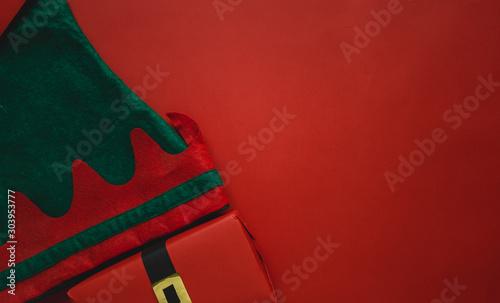 Valokuvatapetti Fondo tradicional navideño con regalo con faja de santa y gorro de elfo navideño