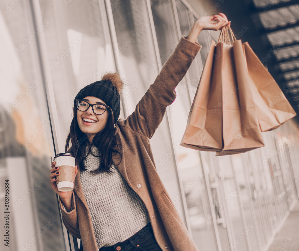 Fototapeta Beautiful fashionable woman drink coffee walking near mall with shopping bags.