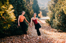 Two Funny Ballerinas Practicing And Falling On Autumn Leaves On The Ground In Sunny Park.