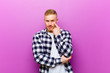 canvas print picture - young blonde man with squared shirt keeping an eye on you, not trusting, watching and staying alert and vigilant