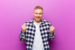 canvas print picture - young blonde man with squared shirt feeling shocked, excited and happy, laughing and celebrating success, saying wow!