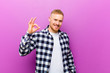 canvas print picture - young blonde man with squared shirt feeling happy, relaxed and satisfied, showing approval with okay gesture, smiling