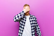 canvas print picture - young blonde man with squared shirt covering eyes with one hand feeling scared or anxious, wondering or blindly waiting for a surprise