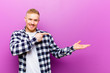 Leinwanddruck Bild - young blonde man with squared shirt smiling, feeling happy, carefree and satisfied, pointing to concept or idea on copy space on the side
