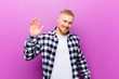 Leinwanddruck Bild - young blonde man with squared shirt smiling happily and cheerfully, waving hand, welcoming and greeting you, or saying goodbye