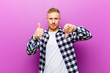 Leinwanddruck Bild - young blonde man with squared shirt feeling confused, clueless and unsure, weighting the good and bad in different options or choices