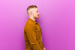 canvas print picture - young blonde man on profile view looking to copy space ahead, thinking, imagining or daydreaming against purple background