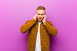 canvas print picture - young blonde man looking angry, stressed and annoyed, covering both ears to a deafening noise, sound or loud music against purple background
