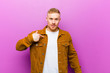 canvas print picture - young blonde man looking happy, proud and surprised, cheerfully pointing to self, feeling confident and lofty against purple background