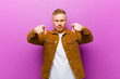 canvas print picture - young blonde man pointing forward at camera with both fingers and angry expression, telling you to do your duty against purple background