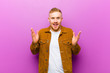canvas print picture - young blonde man looking happy and excited, shocked with an unexpected surprise with both hands open next to face against purple background