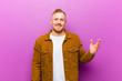 Leinwandbild Motiv young blonde man feeling happy, surprised and cheerful, smiling with positive attitude, realizing a solution or idea against purple background