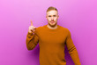 canvas print picture - young blonde man wearing a jumper feeling like a genius holding finger proudly up in the air after realizing a great idea, saying eureka