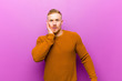 canvas print picture - young blonde man wearing a jumper feeling shocked and astonished holding face to hand in disbelief with mouth wide open
