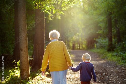 Canvastavla Elderly grandmother and her little grandchild walking together in sunny summer park