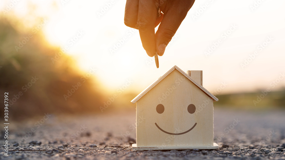 Fototapeta Hand putting golden coin to wood home model at sunset background .saving money and growing business finance concept.