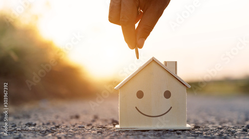 Fotografía  Hand putting golden coin to wood home model at sunset background