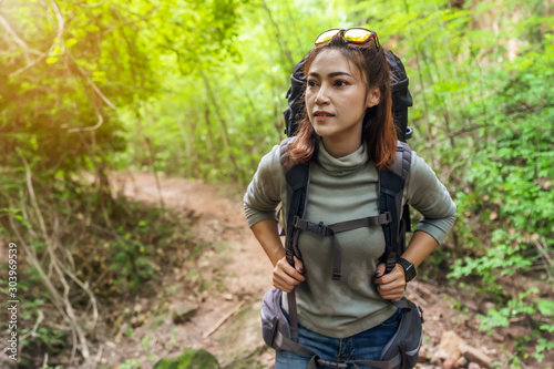 Canvastavla woman traveler with backpack looking to the side walking in the forest