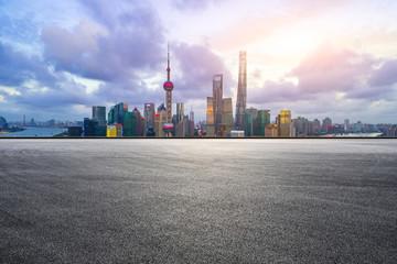Empty asphalt race track and modern city skyline in Shanghai at sunset.