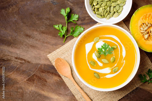Fototapeta Butternut squash soup with pumpkin seed and cream in bowl, top view obraz