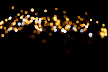 Golden Glitter Bokeh Lights On Black Background, Unfocused. Holiday Time.