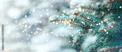 Fotobehang Bomen Christmas tree outdoor with snow, lights bokeh around, and snow falling, Christmas atmosphere.
