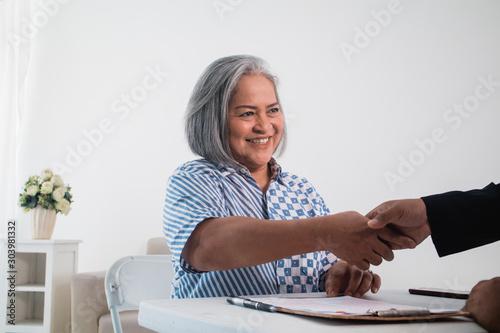 Obraz na plátně  Business partners sit together shake hands sign of make a deal