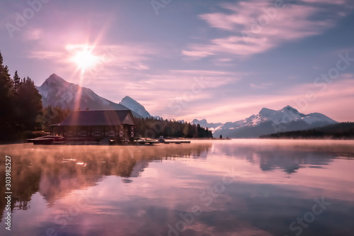 Foto auf AluDibond Rosa hell Colorful sunrise on famous Maligne lake with boat house and white snowy mountains in background. Moody, soft, pink colors of the morning sky, mirror reflection on the lake. Jasper National Park Canada