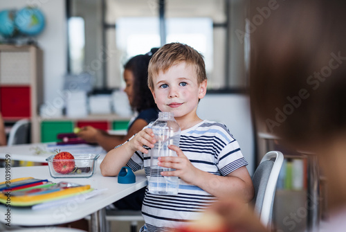 Fotografia Small school boy sitting at the desk in classroom, drinking water