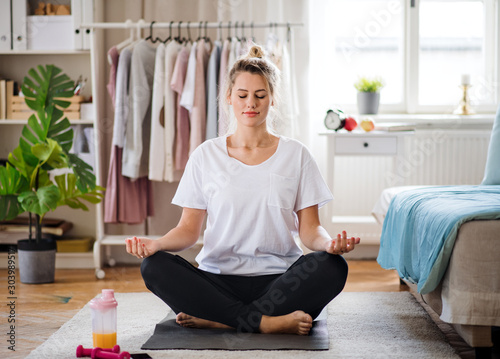 Young woman doing yoga exercise indoors at home, meditating.