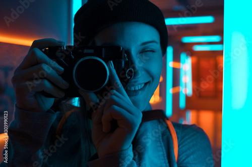 Obraz Smiling female photographer using camera in neon light - fototapety do salonu