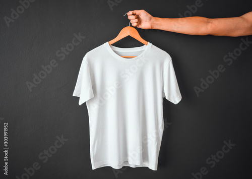 Fotografía  close up of hand holding white color t-shirt hanging on wooden cloth hanger over