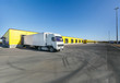 white truck with a white trailer at unloading at the warehouse.Warehouse complex with an asphalt pad and truck with blue sky