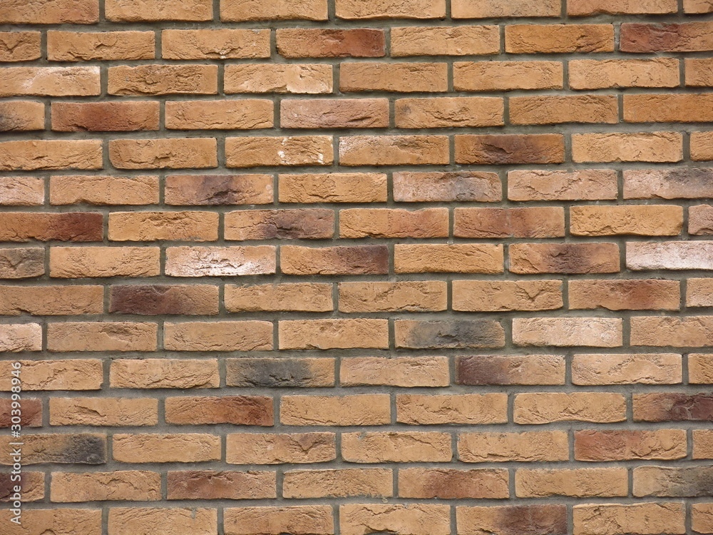 texture of beige or brown brick wall with colored bricks