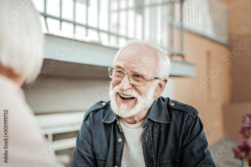 Joyful bearded aged man feeling absolutely happy