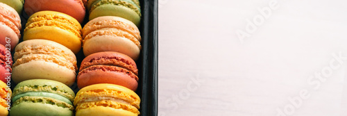 Canvas Prints Macarons Macarons giftbox top view panoramic banner white wooden background.