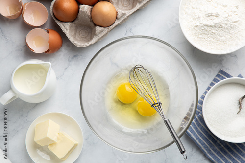 Photo baking cake ingredients (eggs, flour, sugar, butter and milk) on white table