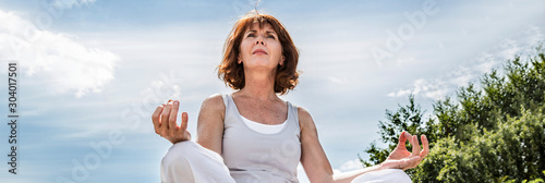 Fototapeta beautiful middle aged woman sitting in yoga lotus position, banner obraz