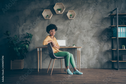 Obraz Full length photo of cool afro american girl college student sit table chair start work high-school presentation feel clever in office loft workstation wear yellow shirt green pants - fototapety do salonu