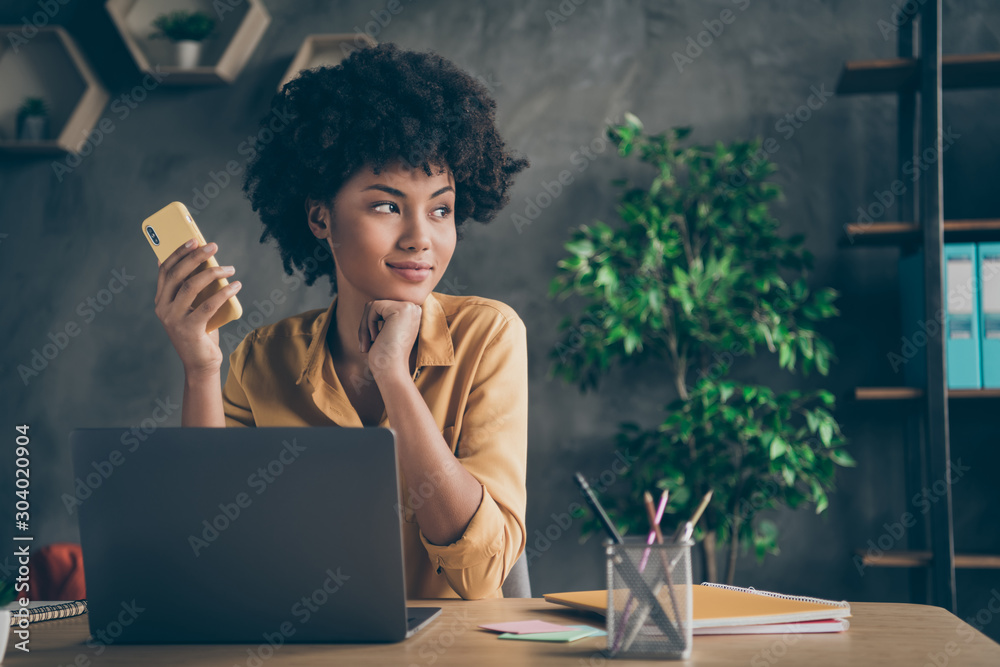 Fototapeta Photo of cheerful positive mixed-race dreamy worker looking wistfully into window sitting at desktop with laptop and pens on table