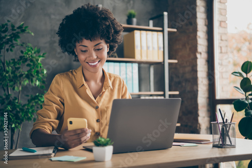 Obraz Photo of cheerful professional business lady in yellow shirt working as smm manager in a large international company browsing through telephone in search of appropriate content - fototapety do salonu