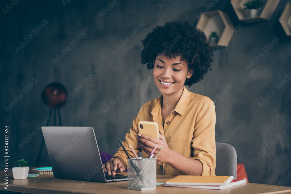 Fototapeta Photo of cheerful positive entrepreneur smiling toothily seeing message from her boss praising her about project finished and startup realized