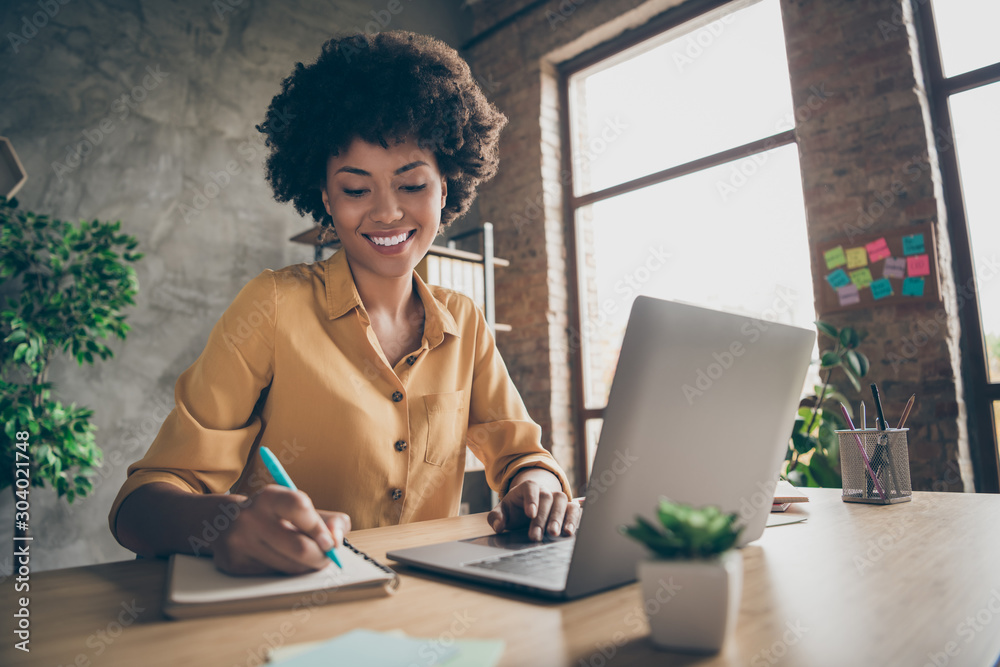 Fototapeta Photo of cheerful pretty cute nice girlfriend having been employed to job as executive smiling toothily sitting at desktop with laptop noting down important information