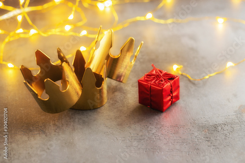 Photo Three gold crowns and red gift box for concept of Epiphany or Dia de Reyes Magos ,  where in Spain giving gift a kids