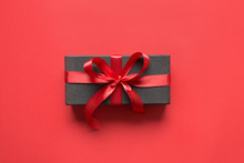 Black Gift Box Wrapped With Red Ribbon On Red Surface.